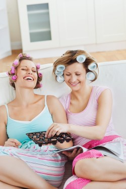 Two women hang out together on a couch with curlers in their hair, eating chocolate.