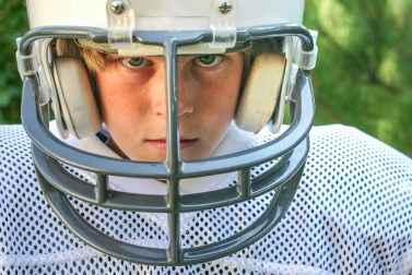 A young boy in a football uniform stares at the camera.