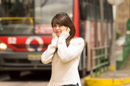 A young woman in a busy city covers her ears.