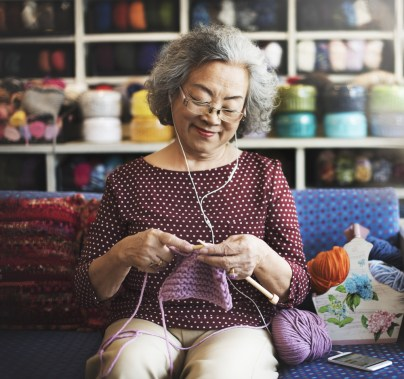 A woman knits happily while listening to headphones.