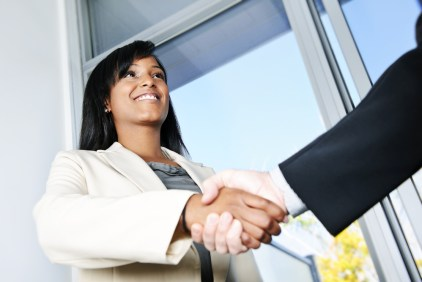A black woman shakes hands with a white hand.