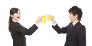 A photo of a Chinese businessman and businesswoman toasting alcoholic beverages while dressed in professional attire.