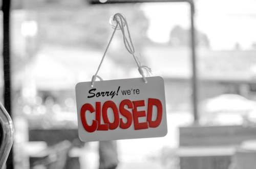 "A black and white photo of a storefront with a sign on the door that reads, ""sorry, we're closed."""