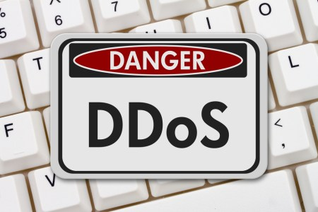 "A keyboard with a warning sign in front of it that reads, ""Danger! DDoS."""