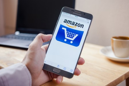 A photo of a person holding a cell phone with an Amazon shopping cart on the screen.