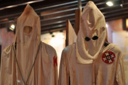 Two KKK robes hung up on a coat rack.