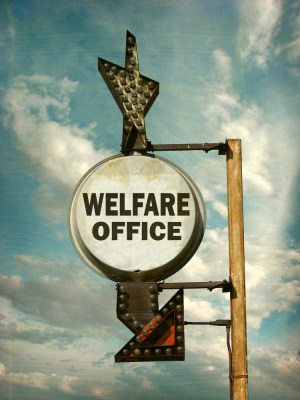 """A sign with an arrow that reads, """"welfare office."""""""
