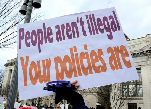 "A protester holds up a sign that reads, ""people aren't illegal; your policies are."""