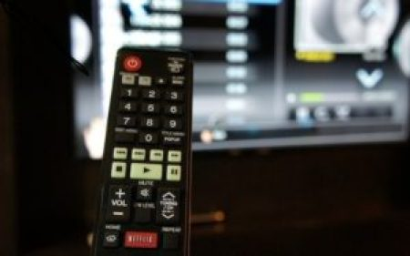 A person holding a remote with a smart TV in the background.