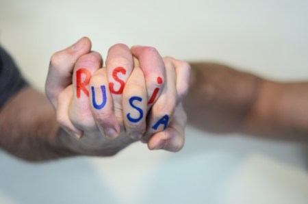 "Two hands with fingers interlaced. The words ""Russia"" and ""USA"" are painted on the fingers."