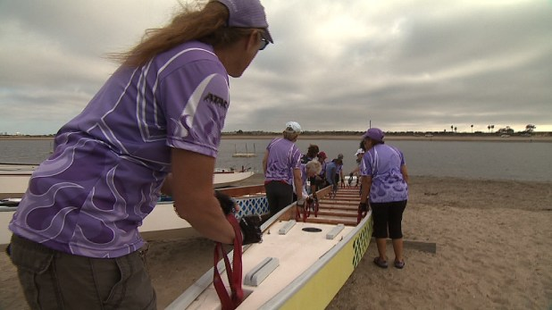 Cheance Adair leads the Team Survivor Sea Dragons as they put their boat in the water on Fiesta Island. July 1, 2014. Credit: Guillermo Sevilla/KPBS.
