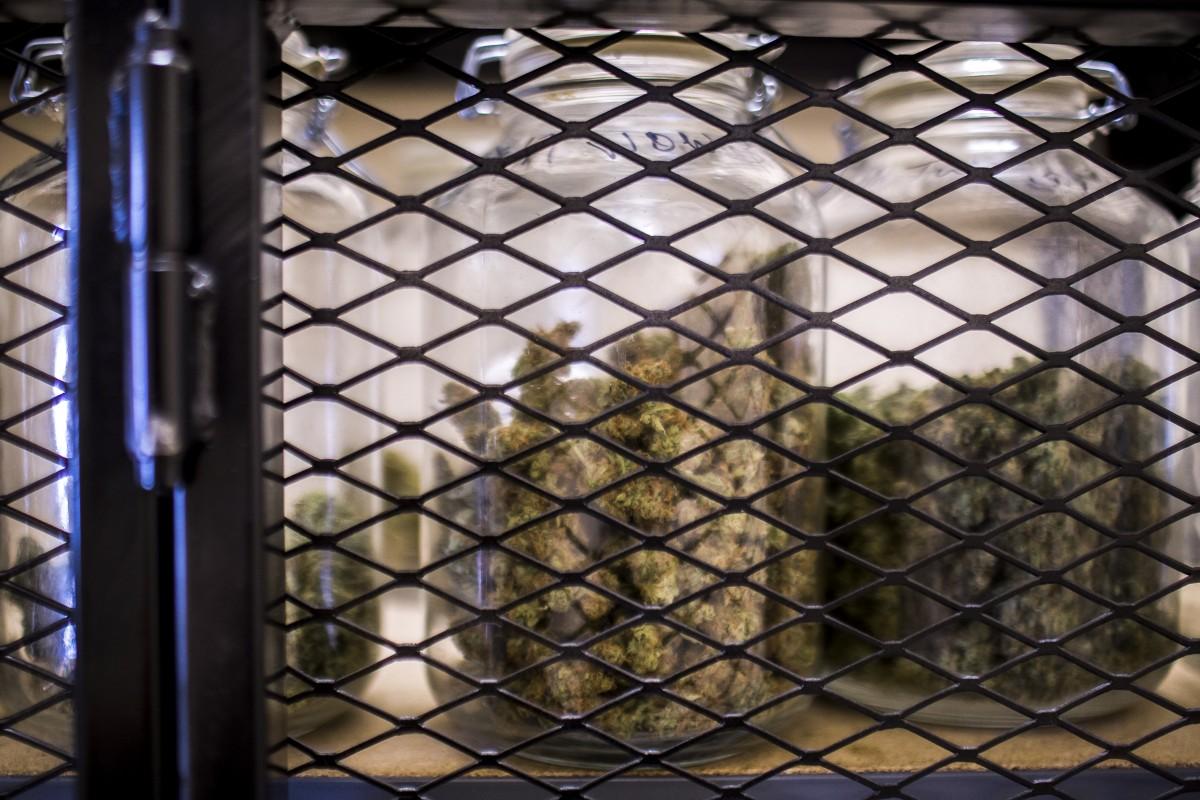 Jars of medical marijuana are kept locked behind a metal gate in a dispensary in Missoula, Montana. Martin do Nascimento/News21
