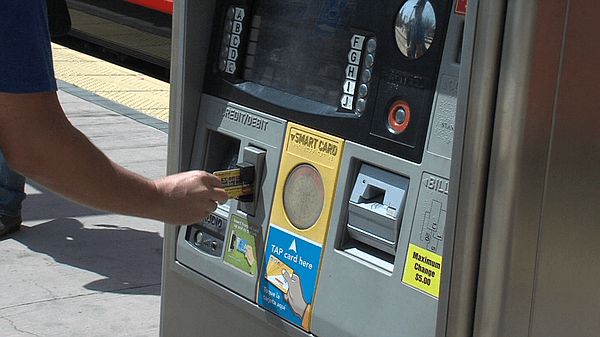 An MTS rider swipes his credit card at an MTS ticket machine in April 2013. Katie Schoolov, KPBS