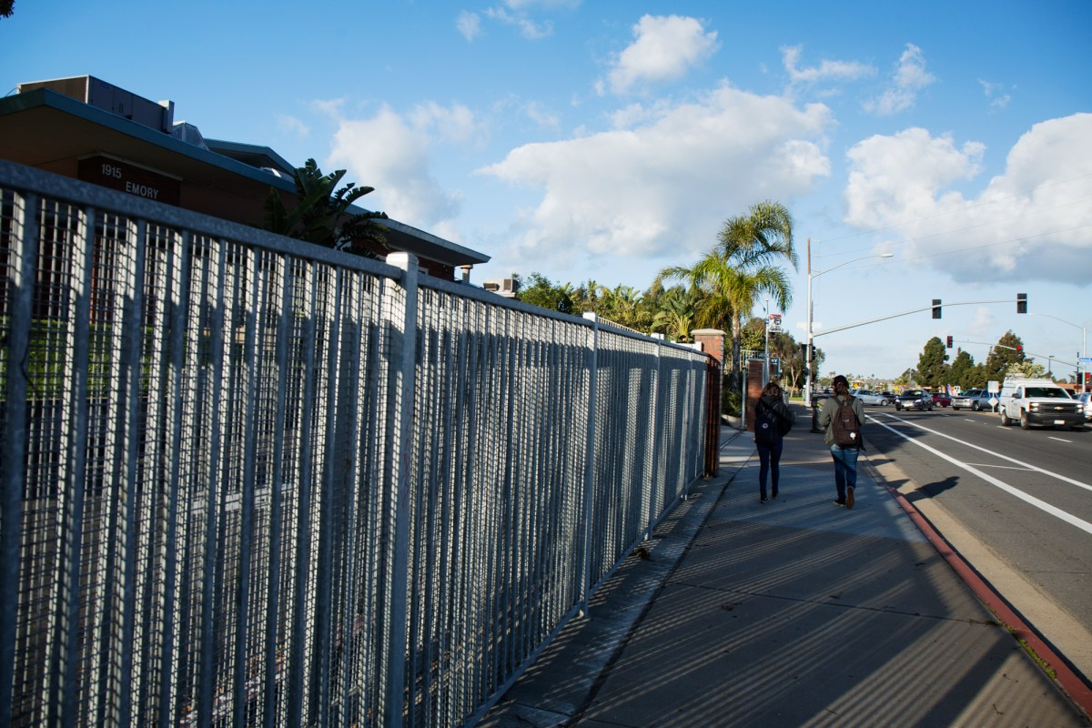 Two students walk past the entrance of Emory Elementary, a school in the South Bay Union School District. In 2016, the district reported 20 percent of its students were homeless. Feb. 23, 2017. Megan Wood, inewsource.