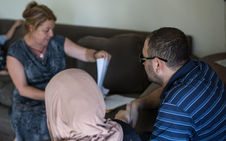 Translator and family friend, Lina Abi-Samra, reviews the lease for the new three-bedroom apartment of Mostafa Inezan (far right), his wife (left) and their five sons, July 25, 2017. Photo by Megan Wood, inewsource.