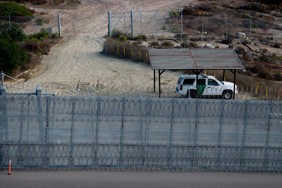 A Border Patrol agent vehicle sits between secondary fencing, which includes concertina wire at the top and bottom, and a basic chain-link fence, known as tertiary fencing. Photo was taken on Aug. 16, 2017. (Brandon Quester/inewsource)