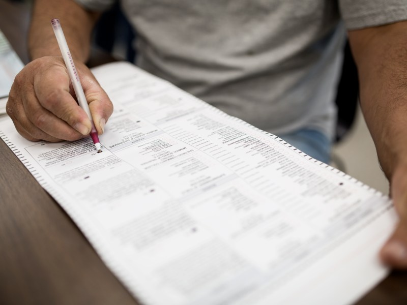 A voter in City Heights fills out a ballot at the City Heights/Weingart Library on June 5, 2018. (Megan Wood/inewsource)