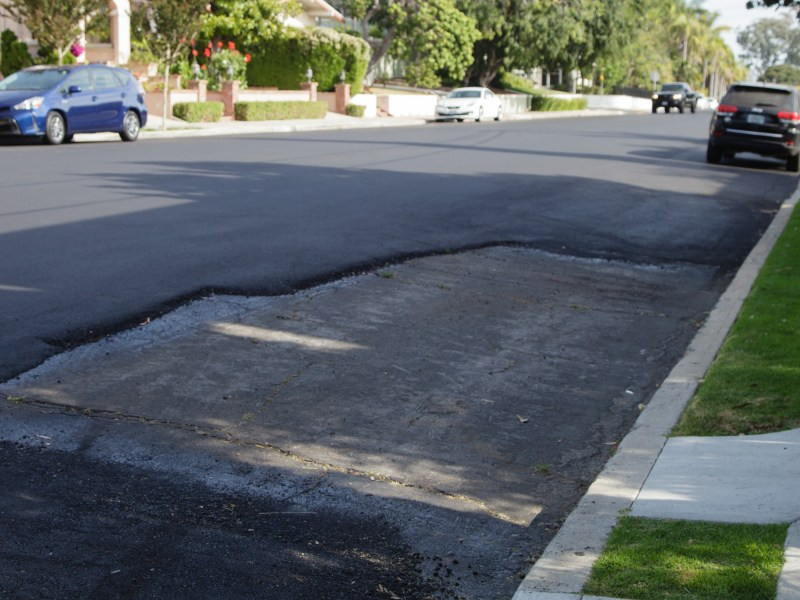 An unpaved section of road is seen on Brant Street in San Diego, where workers paved around a car that was parked rather than towing it, July 31, 2019.