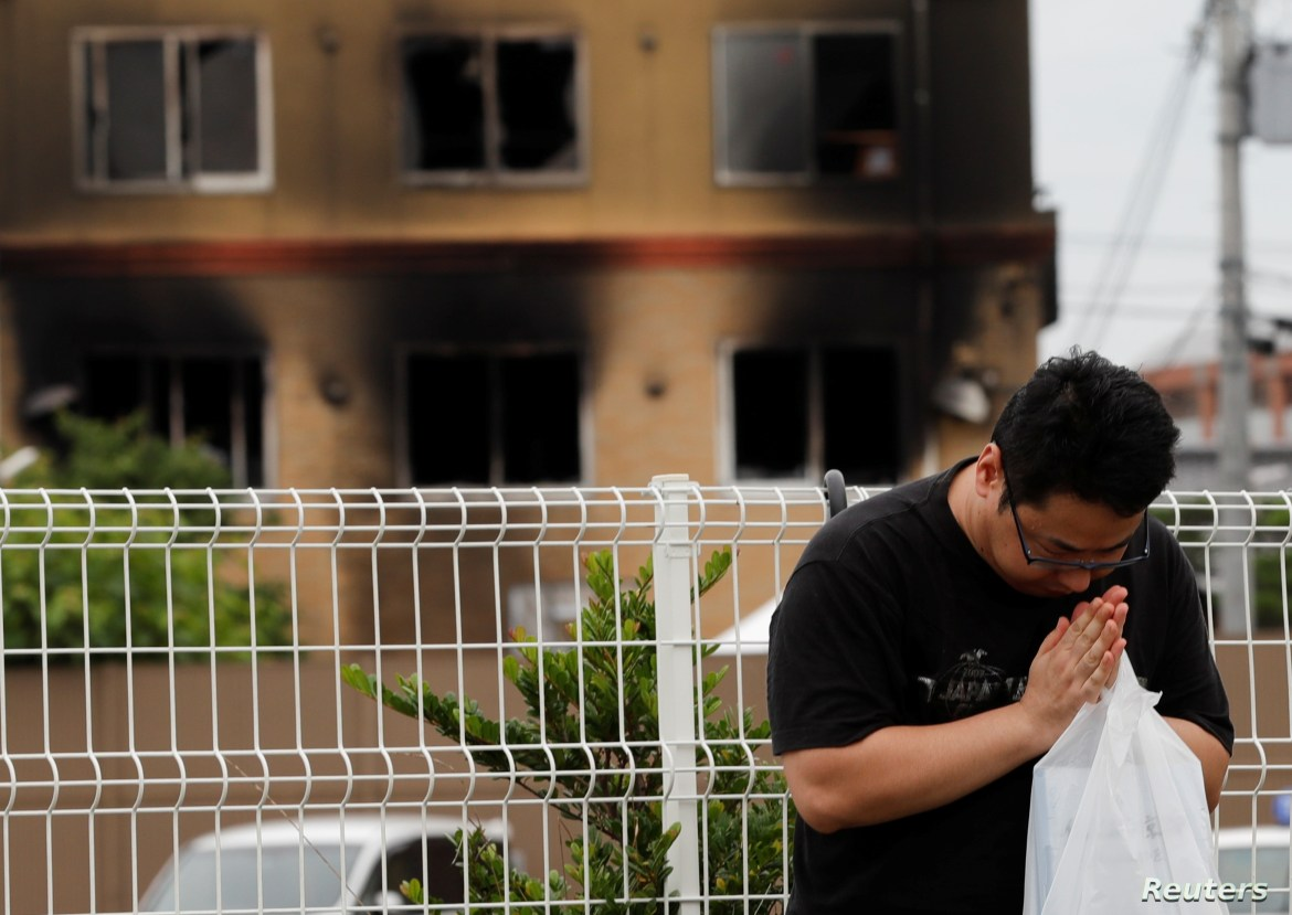A man prays for victims in front of the torched Kyoto Animation building in Kyoto, Japan, July 20, 2019.