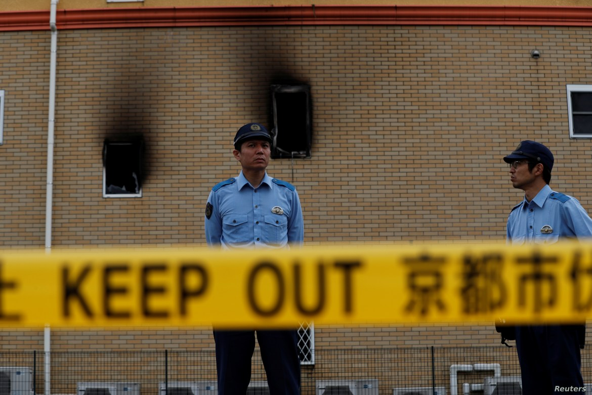 Policemen stand behind a police line at the torched Kyoto Animation building in Kyoto, Japan, July 20, 2019.
