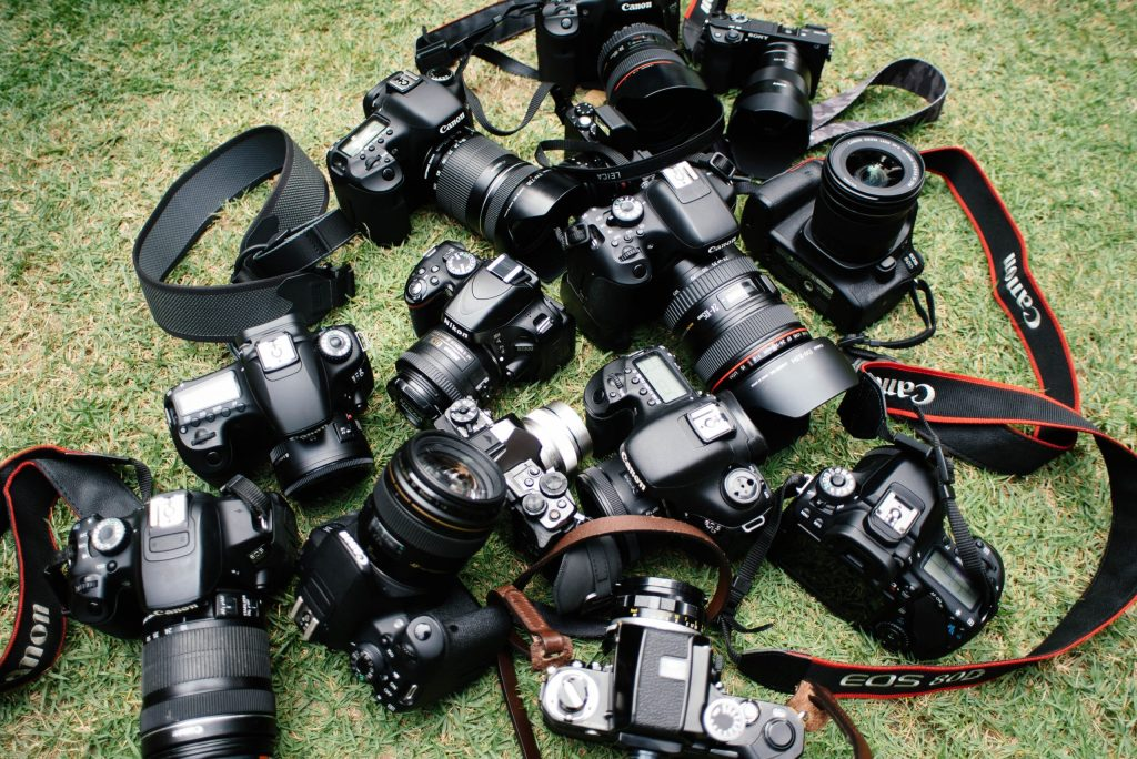 Leveral cameras lying in the grass indicating the importance of FSBO pictures.