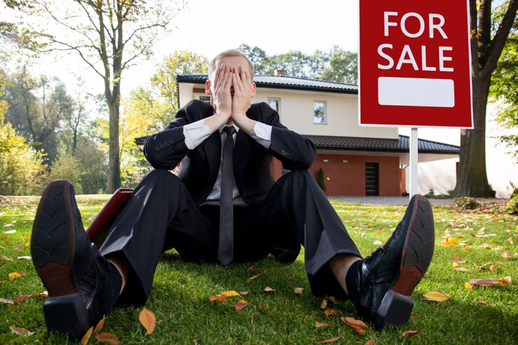 Man sitting on lawn with hands on face very sad and frustrated. For sale by owner having problem with selling their house