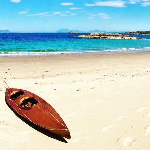 White sandy beach and turquoise sea with wooden kayak on west of Scotland
