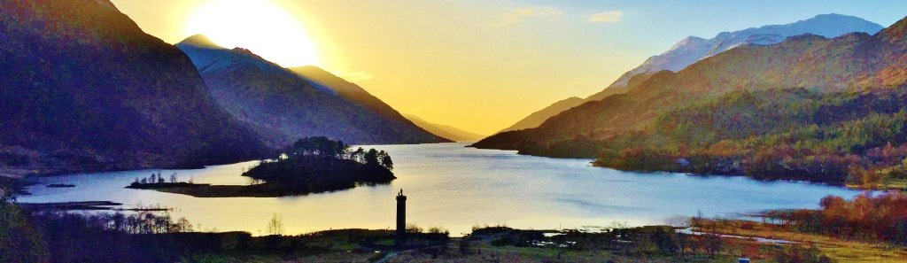 Sunset over Scottish Loch Shiel surrounded by mountains with monument in foreground