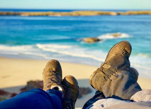 Two pairs of legs and walking boots resting with white sandy beach and turquoise sea in the background