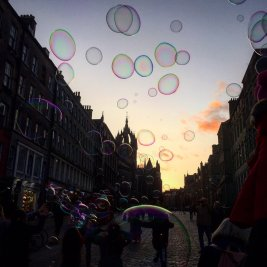 Colourful bubbles float above Edinburgh's oldest street with silhouette of St Giles Cathedral against sunset