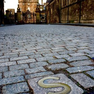 Letter S in cobblestones in front of historic palace