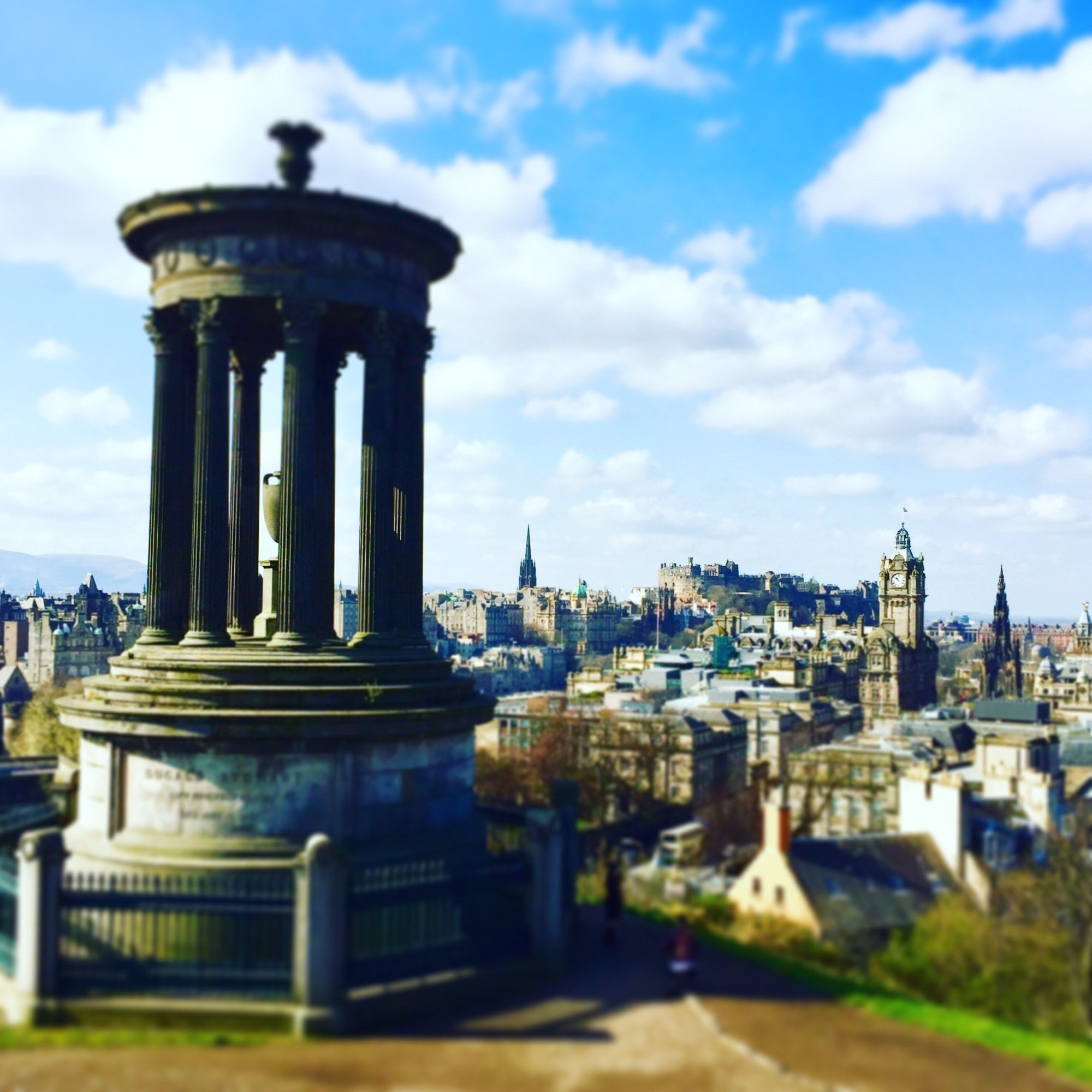 Panoramic view of Edinburgh city with monument in foreground