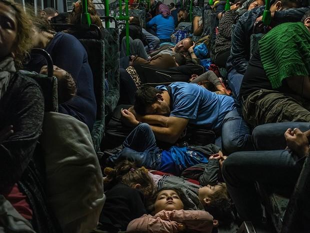 Grupo de refugiados dorme no chão de um ônibus após deixar Budapeste em direção à Viena, na Áustria (Foto: Mauricio Lima/The New York Times/The Pulitzer Prize)