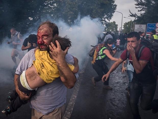 Um homem tenta proteger uma criança após ataque da polícia na fronteira em Horgos, na Sérvia (Foto: Sergey Ponomarev/The New York Times/The Pulitzer Prize)