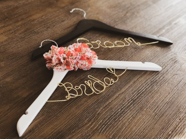 White Bride hanger with 2 Red Floral Pattern Flowers and Gold Wire, and Black Groom Hanger with Gold Wire