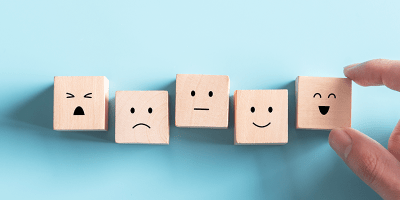 Wooden blocks with a transition from sad to happy faces