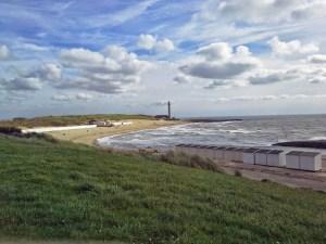 Meer und Deich in Westkapelle mit Strandhäuschen und neuem Leuchtturm im Hintergrund