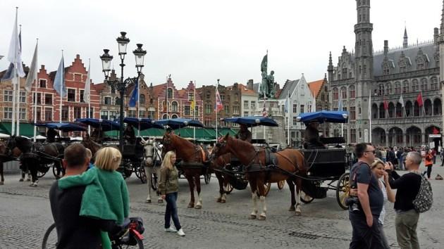 Marktplatz von Brügge mit Touristen und Pferdedroschken