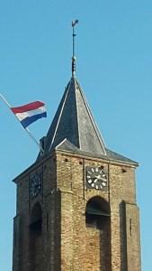 Niederländische Fahne weht am Kirchturm von Aagtekerke zum Königstag