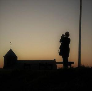 Frau mit Kirche Zoutelande in Abenddämmerung