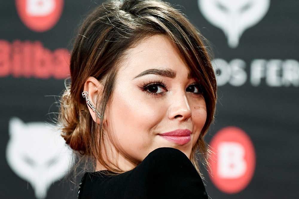 Danna Paola stretches out on the sand to show off her tan, her tattoos and her new bikini