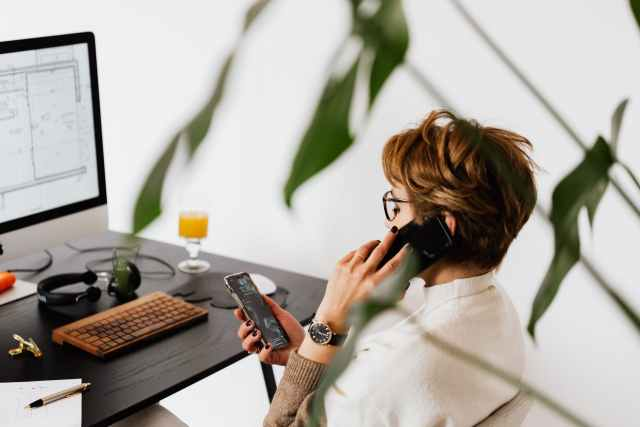 busy female talking on smartphone and checking messages during work in contemporary office