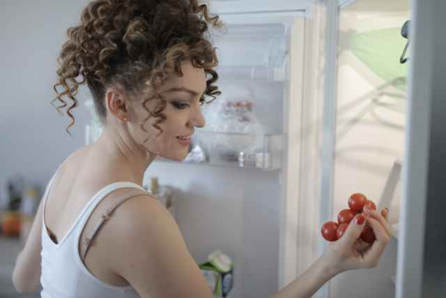 smiling woman with sprig of ripe red grape in kitchen