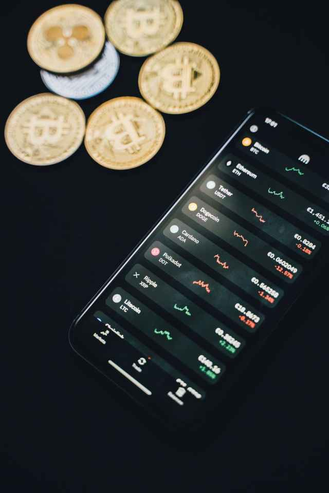 coins scattered near smartphone with financial charts on screen Mercosur: aranceles y relacionamiento