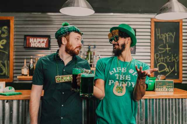 positive young multiethnic men chatting and drinking beer in pub on saint patricks day  Irlanda