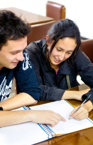 People in a library doing homework - both smiling