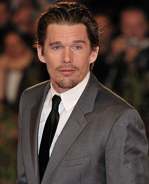 A Caucasian male with dark slick hair, wearing a two-piece gray suit, with a white shirt and black tie.