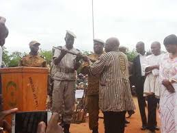Simon handing over symbolically a riffle to police officer