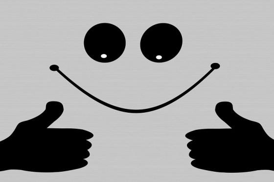 Icono de sonrisa y dos manos con el pulgar hacia arriba