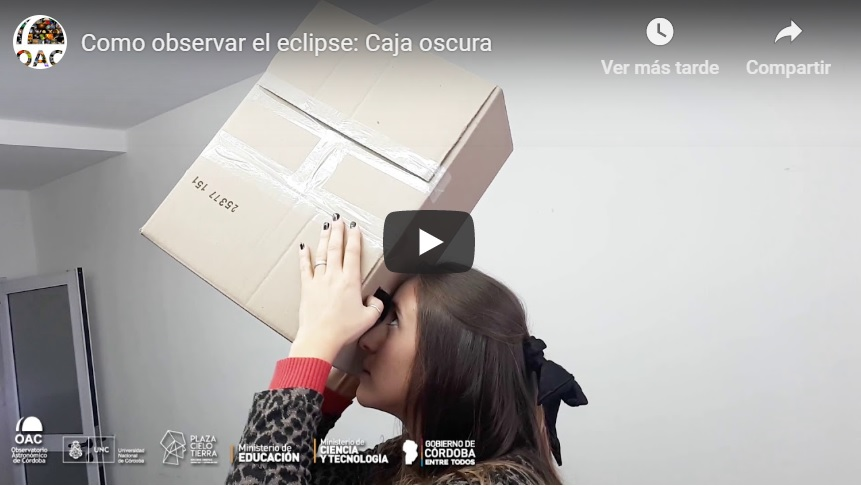 mujer mirando un eclipse de sol a través de una cámara oscura de fabricación casera
